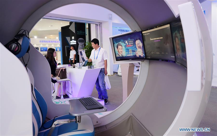 A visitor (R) consults at the stand of an educational organization during the World Artificial Intelligence Conference (WAIC) 2018 in Shanghai, east China, Sept. 17, 2018. The three-day conference has attracted experts, scholars and entrepreneurs from nearly 40 countries and regions. More than 200 leading companies in AI participated in the conference and the exhibition. (Xinhua/Fang Zhe)