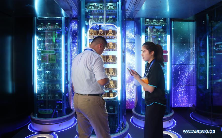 An exhibitor shows how to buy goods at an intelligent market during the World Artificial Intelligence Conference (WAIC) 2018 in Shanghai, east China, Sept. 17, 2018. The three-day conference has attracted experts, scholars and entrepreneurs from nearly 40 countries and regions. More than 200 leading companies in AI participated in the conference and the exhibition. (Xinhua/Ding Ting)