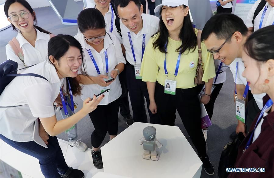 Visitors interact with a robot during the World Artificial Intelligence Conference (WAIC) 2018 in Shanghai, east China, Sept. 17, 2018. The three-day conference has attracted experts, scholars and entrepreneurs from nearly 40 countries and regions. More than 200 leading companies in AI participated in the conference and the exhibition. (Xinhua/Fang Zhe)