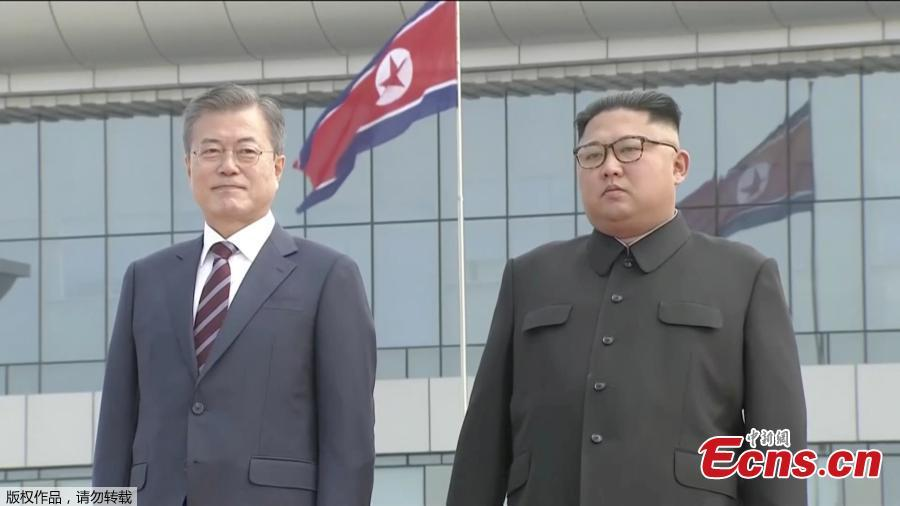 In this image made from video, South Korean President Moon Jae-in, left, poses with the Democratic People\'s Republic of Korea leader Kim Jong Un for a photo on the podium upon arrival in Pyongyang, Sept. 18, 2018. Moon landed in Pyongyang for his third summit this year with Kim. (Photo/Agencies)