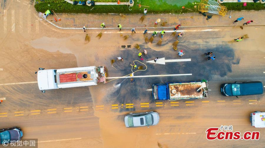 People clear a muddy road in the aftermath of Super Typhoon Mangkhut in Zhuhai City, South China's Guangdong Province, Sept. 17, 2018. (Photo/VCG)