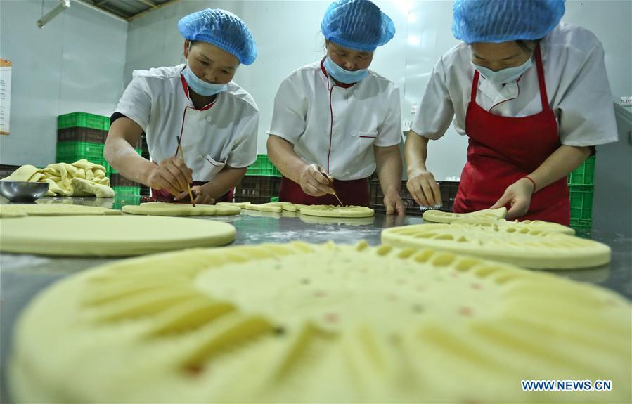 Staff make traditional moon cakes at a food processing workshop in Zhangye, northwest China\'s Gansu Province, on Sept. 18, 2018. Making traditional moon cakes before the Mid-Autumn Festival dates back to a thousand years in Zhangye. (Xinhua/Wang Jiang)