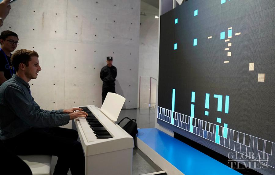 A visitor tries out an AI keyboard, which can produce music based on the prelude they just played. (Photo: Yang Hui/GT)
