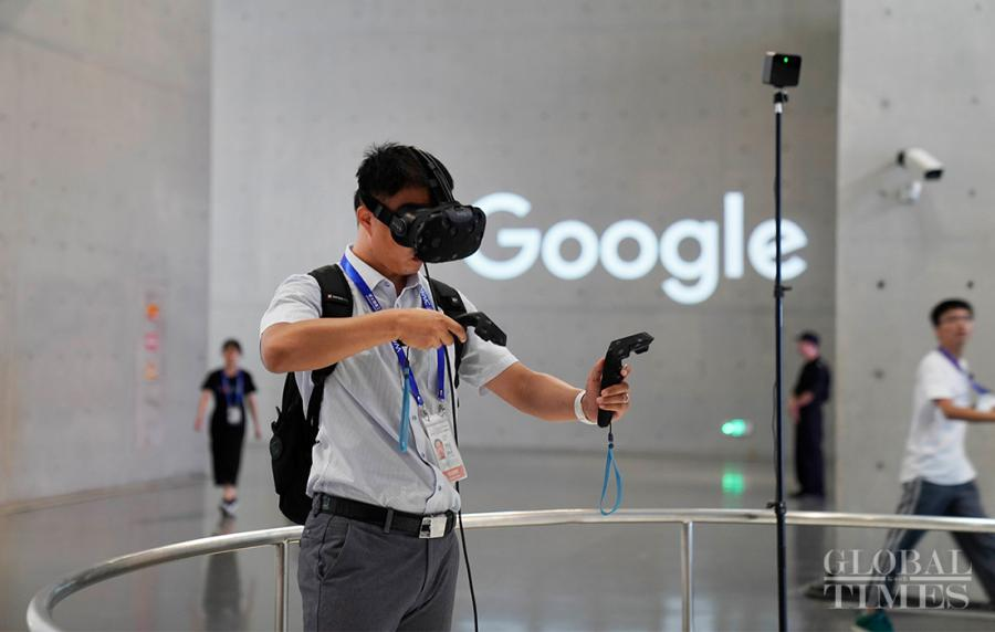 A visitor paints by using AI grips and a pair of VR glasses.  (Photo: Yang Hui/GT)