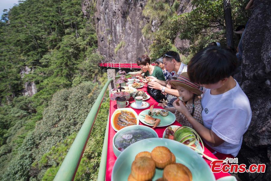 A view of a restaurant built on a cliff at Longquan Mountain in Zhejiang Province, Sept. 19, 2018. Over 100 tourists became the first customers of the newly opened restaurant and had food on suspended plank roads while enjoying the great view of the mountain. Longquan is the highest peak in the Yangtze River Delta. (Photo: China News Service/Yang Chen)