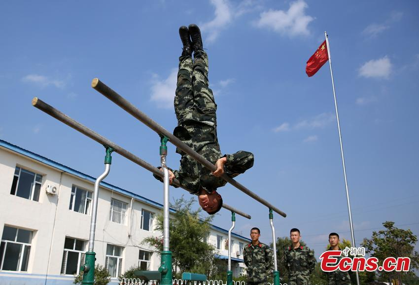 Armed police Kang Liming shows his skills on parallel bars in Meihekou City, Northeast China's Jilin Province. The Kang brothers joined the army together and have won a number of awards although they have different personalities and gifts. (Photo: China News Service/Liang Yonggang)