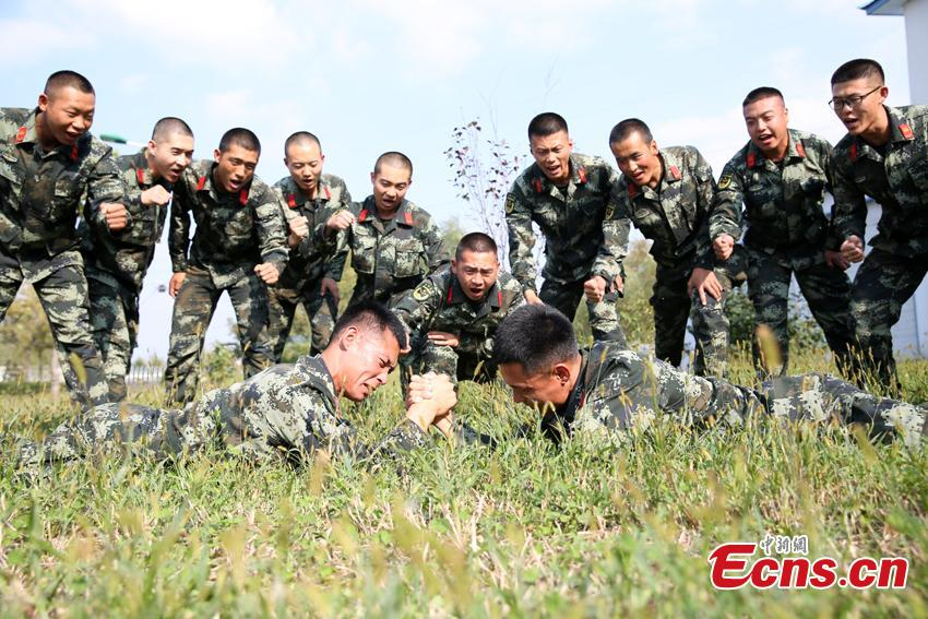Armed police Kang Lidong and Kang Liming, who are twin brothers, have an arm wrestling competition in Meihekou City, Northeast China's Jilin Province. The Kang brothers joined the army together and have won a number of awards although they have different personalities and gifts. (Photo: China News Service/Liang Yonggang)
