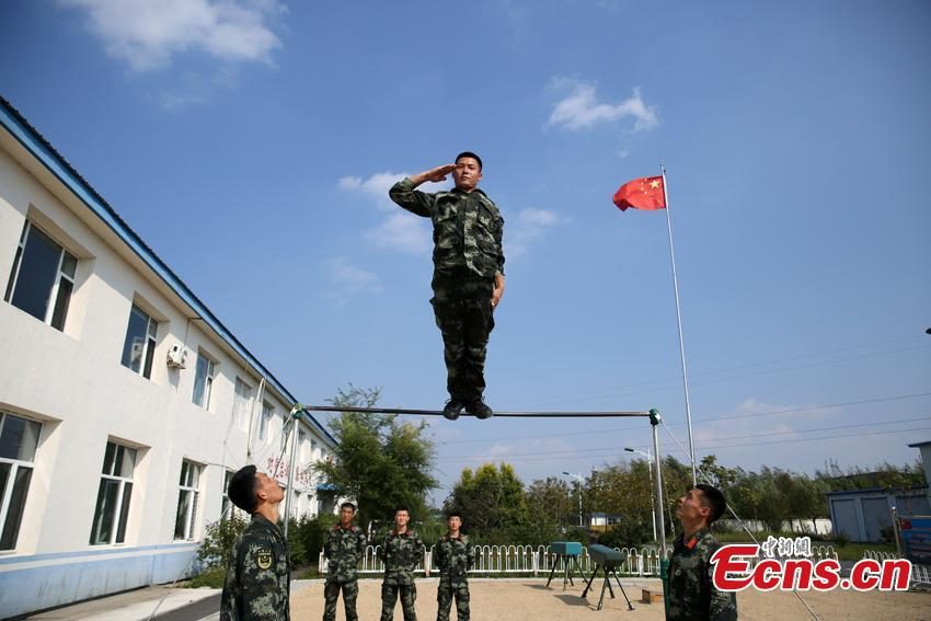 Armed police Kang Lidong salutes while standing on a horizontal bar during training in Meihekou City, Northeast China's Jilin Province. The Kang brothers joined the army together and have won a number of awards although they have different personalities and gifts. (Photo: China News Service/Liang Yonggang)