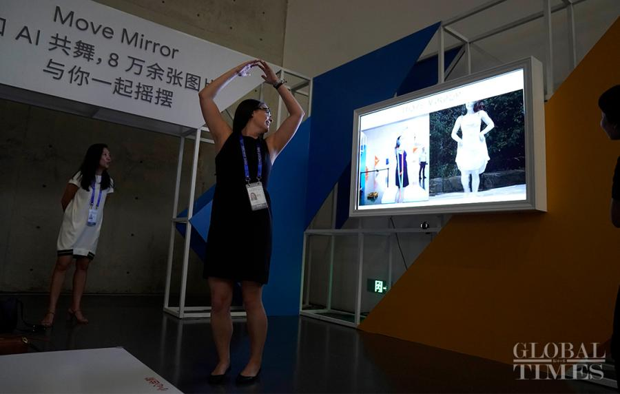 Visitors test out an AI software that matches poses to photos.  (Photo: Yang Hui/GT)