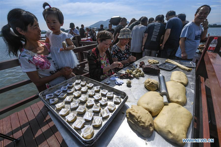 Staff members of a local cake shop make traditional moon cakes in Dinghe Village of Tangqi Township in Hangzhou, capital of east China\'s Zhejiang Province, Sept. 19, 2018. The locals held various folk activities to celebrate the coming of China\'s first Farmers\' Harvest Festival and the Mid-Autumn Festival. (Xinhua/Xu Yu)