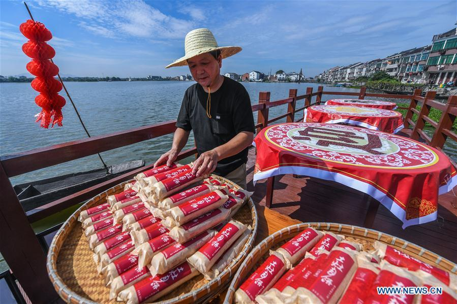 A staff member of a local cake shop displays traditional moon cakes in Dinghe Village of Tangqi Township in Hangzhou, capital of east China\'s Zhejiang Province, Sept. 19, 2018. The locals held various folk activities to celebrate the coming of China\'s first Farmers\' Harvest Festival and the Mid-Autumn Festival. (Xinhua/Xu Yu)