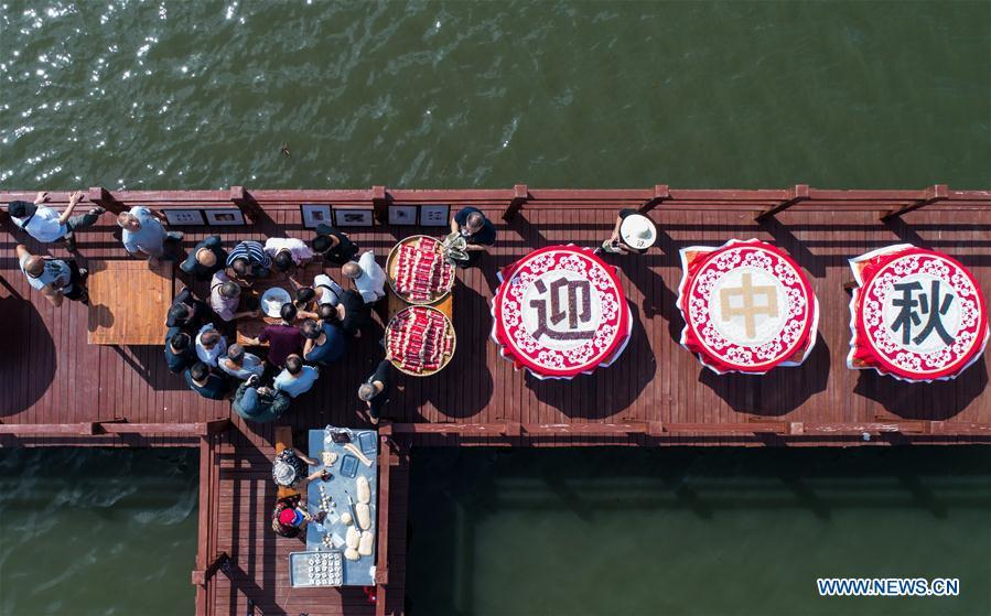 Aerial photo taken on Sept. 19, 2018 shows local people attending a folk activity in Dinghe Village of Tangqi Township in Hangzhou, capital of east China\'s Zhejiang Province. The locals held various folk activities to celebrate the coming of China\'s first Farmers\' Harvest Festival and the Mid-Autumn Festival. (Xinhua/Xu Yu)