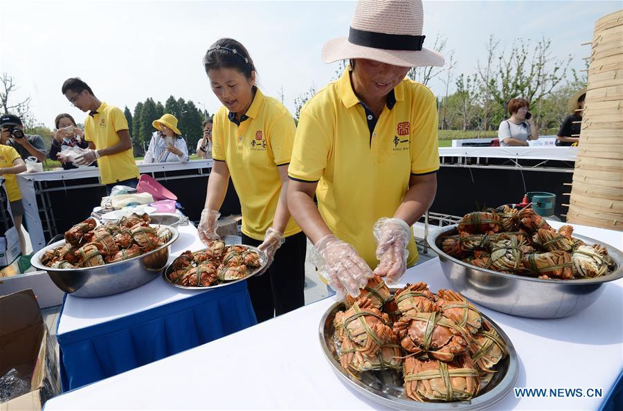 Staff members prepare dishes made from Chinese mitten crabs during a tourist festival held ashore the Yangcheng Lake in Xiangcheng District of Suzhou, east China\'s Jiangsu Province, Sept. 19, 2018. The Chinese mitten crabs inhabiting Suzhou\'s Yangcheng Lake are a popular cooking ingredient for many food lovers. In the annual event which kicked off here on Wednesday, tourists will be able to have a taste of this year\'s first Chinese mitten crabs ready to serve the table, while the official netting of Yangcheng Lake crabs will begin on Sept. 21. (Xinhua/Hao Qunying)