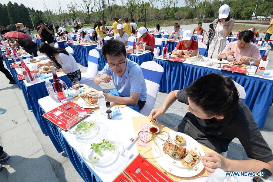 Tourists enjoy dishes made from Chinese mitten crabs during a tourist festival held ashore the Yangcheng Lake in Xiangcheng District of Suzhou, east China\'s Jiangsu Province, Sept. 19, 2018. The Chinese mitten crabs inhabiting Suzhou\'s Yangcheng Lake are a popular cooking ingredient for many food lovers. In the annual event which kicked off here on Wednesday, tourists will be able to have a taste of this year\'s first Chinese mitten crabs ready to serve the table, while the official netting of Yangcheng Lake crabs will begin on Sept. 21. (Xinhua/Hao Qunying)