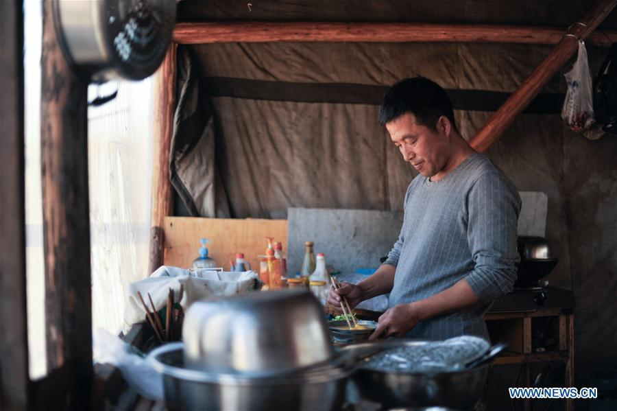 Forester Wang Liang prepares lunch in Yue\'anli Forest Farm of Genhe forestry bureau in the Greater Khingan Mountains of north China\'s Inner Mongolia Autonomous Region, Sept. 18, 2018. Staff members at Yue\'anli Forest Farm are responsible for the conservation and breeding work of reindeer in China. (Xinhua/Yu Yang)