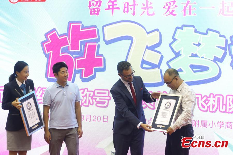 Marco Frigatti (second from right), Global Records senior vice-president of Greater China at Guinness World Records, grants certificates to the organizers of the paper aircrafts activity, in Beijing, Sept 20, 2018. Children from 22 provinces and cities made more than 60,000 paper planes, of which 14,285 were selected to create a line measuring 3,029.02 meters in length. It\'s the world\'s longest line of paper aircrafts and set a new Guinness World Record. The project was initiated by the China Children and Teenagers\' Fund and the Sister Ma Food Company in May. (Photo: China News Service/Sheng Jiapeng)
