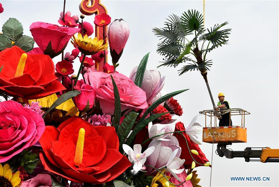 A constructor decorates an artificial flower basket at the Tiananmen Square in Beijing, capital of China, Sept. 20, 2018. A 17-meter-tall installation in the shape of a flower basket with a diameter of 50 meters at the bottom is placed at the center of the Tiananmen Square as a decoration for China\'s upcoming National Day holiday. (Xinhua/Luo Xiaoguang)