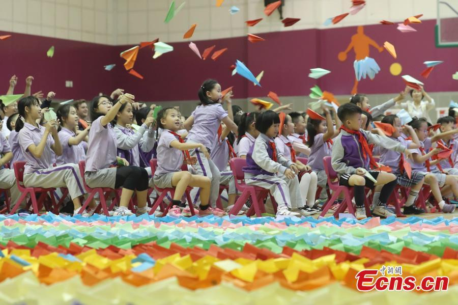 Primary school students fly paper aircrafts during an attempt to set a world record in Beijing, Sept. 20, 2018. Children from 22 provinces and cities made more than 60,000 paper planes, of which 14,285 were selected to create a line measuring 3,029.02 meters in length. It\'s the world\'s longest line of paper aircrafts and set a new Guinness World Record. The project was initiated by the China Children and Teenagers\' Fund and the Sister Ma Food Company in May. (Photo: China News Service/Sheng Jiapeng)