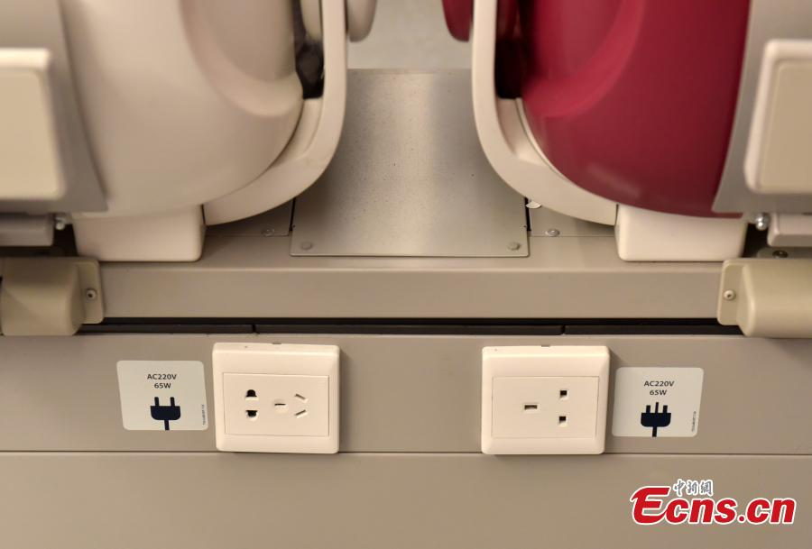 Power sockets suitable for different electrical standards are available in the front of seats on a high-speed train used for the Guangzhou-Shenzhen-Hong Kong Express Rail Link, Sept. 23, 2018. The first-class seats feature soft lighting, seats in different colors, as well as rose patterns on the floor. (Photo: China News Service/Zhang Wei)