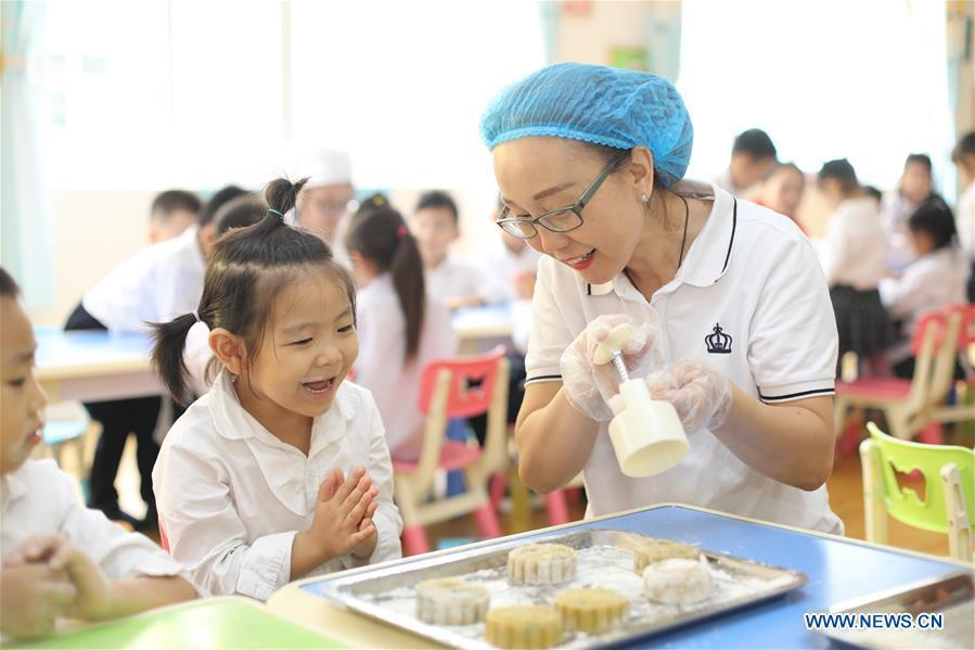 Children learn to make mooncakes at a kindergarten to greet the traditional Mid-Autumn Festival in Gucheng County, north China\'s Hebei Province, Sept. 21, 2018. The Mid-Autumn Festival falls on the 15th day of the eighth month of the Chinese lunar calendar, or Sept. 24 this year. (Xinhua/Zhu Xudong)