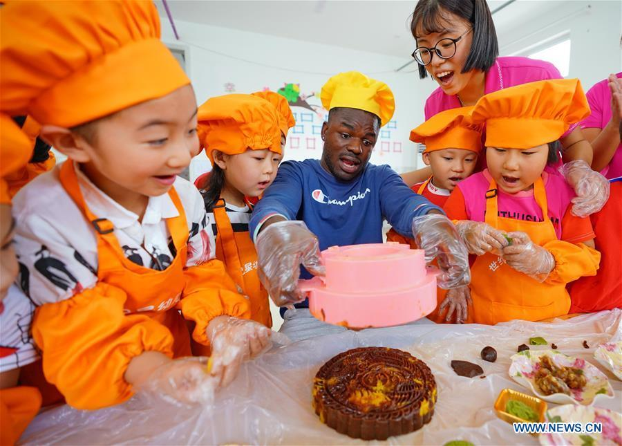 Children learn to make mooncakes at Shijixing kindergarten to greet the traditional Mid-Autumn Festival in Tangshan City, north China\'s Hebei Province, Sept. 21, 2018. The Mid-Autumn Festival falls on the 15th day of the eighth month of the Chinese lunar calendar, or Sept. 24 this year. (Xinhua/Yang Shiyao)