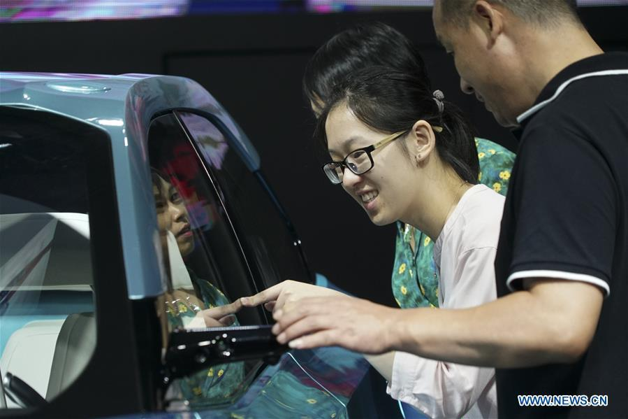 Visitors look at a new-energy vehicle exhibited at the Future of Transportation World Conference in Hangzhou, east China\'s Zhejiang Province, Sept. 20, 2018. (Xinhua)