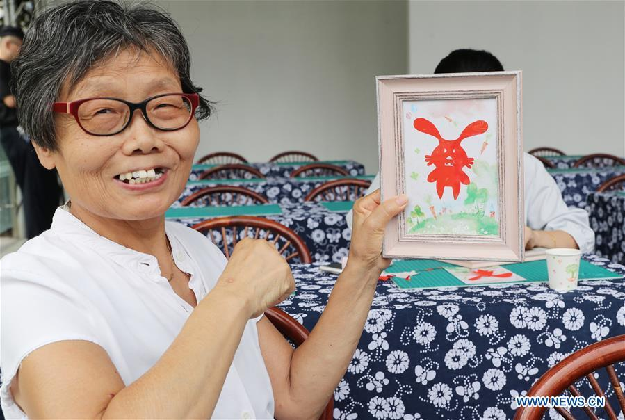 A citizen shows her paper cutting work during a series of activities held to greet Mid-Autumn Festival in Shanghai, east China, Sept. 22, 2018. The Chinese traditional Mid-Autumn Festival falls on the 15th day of the eighth month on the Chinese lunar calendar, which is Sept. 24 this year. (Xinhua/Fang Zhe)