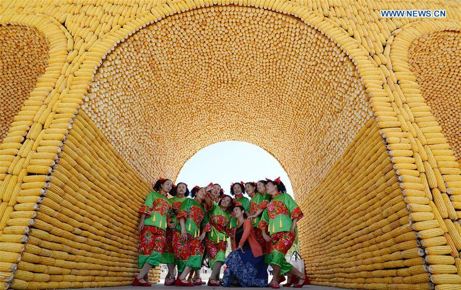 People pose for photos under an archway made of various harvested crops in a tourist spot in Handan, north China\'s Hebei Province, Sept. 22, 2018. China will mark its first Farmers\' Harvest Festival on Sept. 23 this year. From 2018 on, the festival, to be celebrated on the Autumnal Equinox each year, is set to be observed annually to greet the harvest season and honour the agricultural workers. (Xinhua/Hao Qunying)