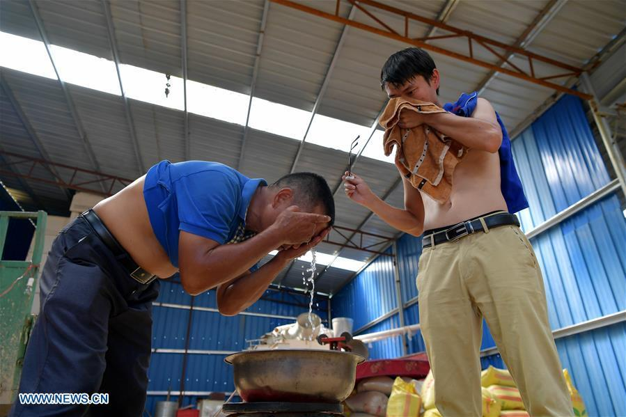 Zhou Xiaolin (L) and Zhou Biao wash their faces after their morning work in Liutian Village of Xinjian District in Nanchang, east China\'s Jiangxi Province, Sept. 20, 2018. When every harvest season for middle-season rice begins in September, Zhou Xiaolin, a rice grower, and his son Zhou Biao will always offer help to other farmers with the harvest, because few families nearby own multiple farm machineries that suffice the workload. Born in Liutian Village, Zhou Xiaolin used to be a carpenter away from home. In 2005, he returned home to take on rice growing. Two years later, Zhou Xiaolin and Zhou Biao expanded the scale of their rice growing by contracting to take over the village\'s uncultivated croplands. To meet the increasing production demand, Zhou bought the first farm machine in the village. Currently, Zhou Xiaolin and Zhou Biao have nearly 50 hectares of farmland under cultivation in the village. Altogether they own two combine harvesters, two rice transplanters and a tractor, which have made production even more efficient. An increasing number of rice growers nearby have started to use Zhou Xiaolin\'s machines and services for a reasonable price. \