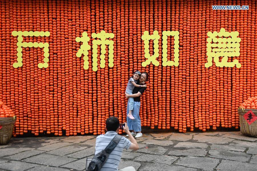 Tourists pose for photos in front of a wall decorated by persimmons at Xixi Wetland National Park in Hangzhou, east China\'s Zhejiang Province, Sept. 22, 2018. China will mark its first Farmers\' Harvest Festival on Sept. 23 this year. From 2018 on, the festival, to be celebrated on the Autumnal Equinox each year, is set to be observed annually to greet the harvest season and honour the agricultural workers. (Xinhua/Huang Zongzhi)