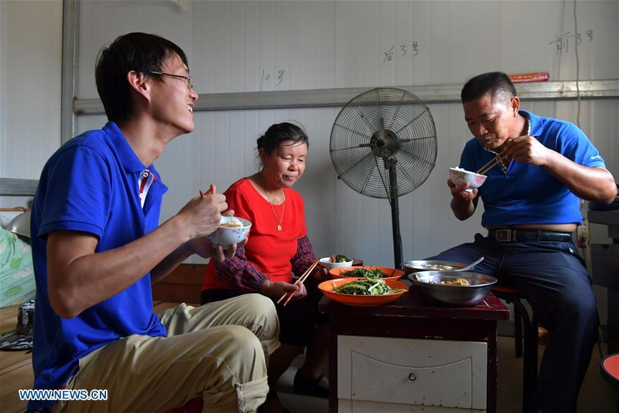 Zhou Xiaolin (R) and and his family have lunch in Liutian Village of Xinjian District in Nanchang, east China\'s Jiangxi Province, Sept. 20, 2018. When every harvest season for middle-season rice begins in September, Zhou Xiaolin, a rice grower, and his son Zhou Biao will always offer help to other farmers with the harvest, because few families nearby own multiple farm machineries that suffice the workload. Born in Liutian Village, Zhou Xiaolin used to be a carpenter away from home. In 2005, he returned home to take on rice growing. Two years later, Zhou Xiaolin and Zhou Biao expanded the scale of their rice growing by contracting to take over the village\'s uncultivated croplands. To meet the increasing production demand, Zhou bought the first farm machine in the village. Currently, Zhou Xiaolin and Zhou Biao have nearly 50 hectares of farmland under cultivation in the village. Altogether they own two combine harvesters, two rice transplanters and a tractor, which have made production even more efficient. An increasing number of rice growers nearby have started to use Zhou Xiaolin\'s machines and services for a reasonable price. \