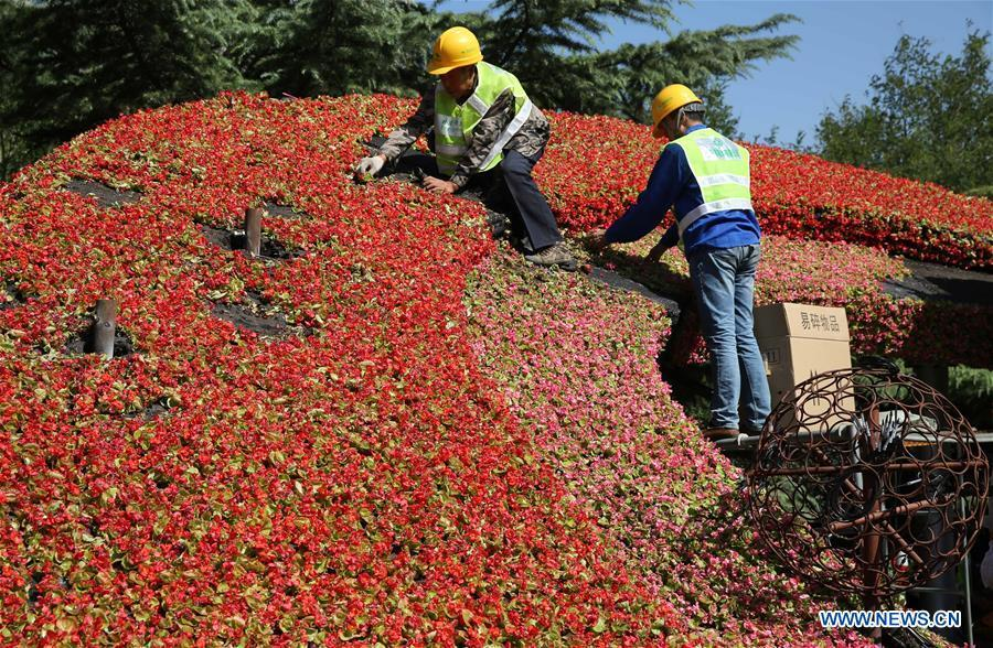 Workers arrange flowers for a decorating parterre in Beijing, capital of China, Sept. 21, 2018. Decorating parterres are set up in Beijing to greet the National Day, which falls on Oct. 1. (Xinhua/Liang Zhiqiang)