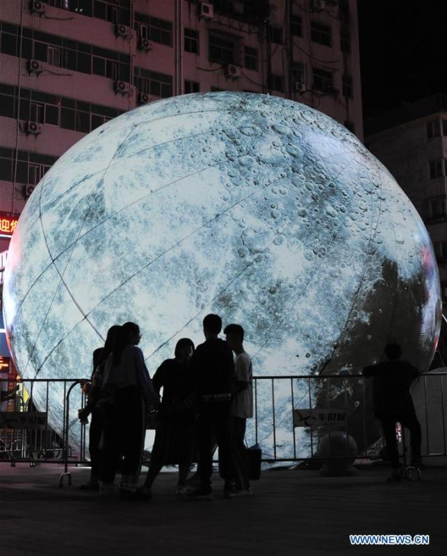 Pedestrians look at a moon installation set up to mark the upcoming Mid-Autumn Festival in front of a department store in Shiyan, central China\'s Hubei Province, Sept. 23, 2018. (Xinhua/Zhang Xinjun)