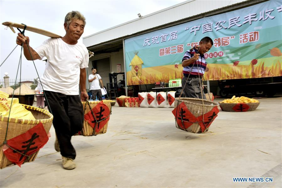 Villagers take part in a grain carrying contest in Changgang Village of the Rucheng community in Rugao, east China\'s Jiangsu Province, Sept. 23, 2018. People across China hold various activities to celebrate the country\'s first Farmers\' Harvest Festival, which falls on Sept. 23 this year. (Xinhua/Wu Shujian)
