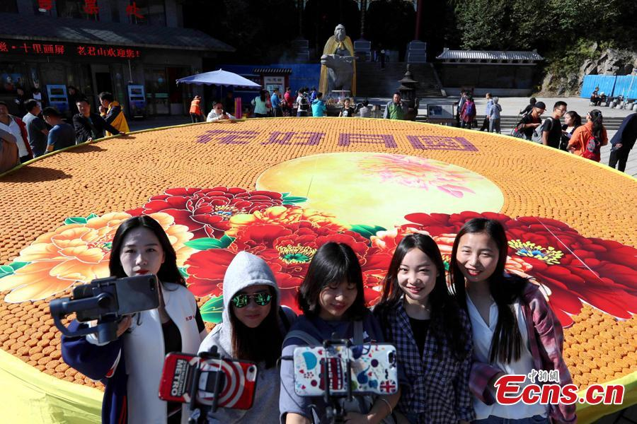 People take photos before a beautiful pattern with Chinese characters of Hua Hao Yue Yuan (Blooming flowers and full moon) spelt out with 9,999 mooncakes at Laojun Mountain, a scenic spot in Luoyang City, Central China's Henan Province, Sept. 23, 2018. (Photo: China News Service/Wang Zhongju)