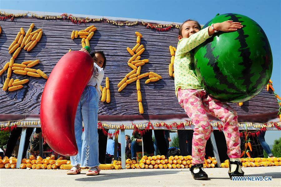 Two girls participate in an activity marking China\'s first Farmers\' Harvest Festival in Zibo, east China\'s Shandong Province, Sept. 23, 2018. People across China hold various activities to celebrate the country\'s first Farmers\' Harvest Festival, which falls on Sept. 23 this year. (Xinhua/Liu Bingyou)