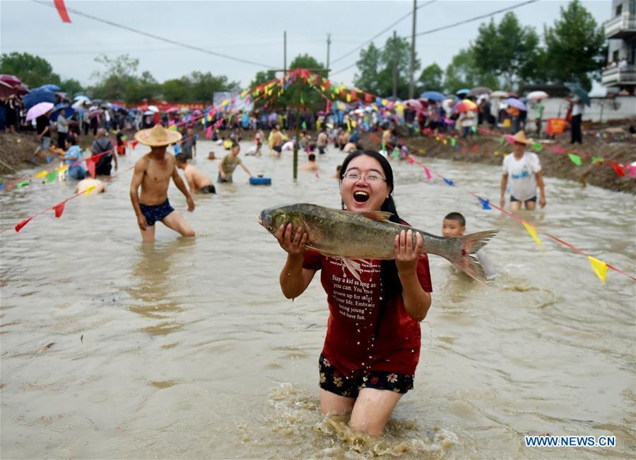 A girl shows a fish she has caught in a bare-hand fish catching contest held in Housangyuan Village of Lyutan Township Wuyi County, east China\'s Zhejiang Province, Sept. 23, 2018. People across China hold various activities to celebrate the country\'s first Farmers\' Harvest Festival, which falls on Sept. 23 this year. (Xinhua/Zhang Jiancheng)