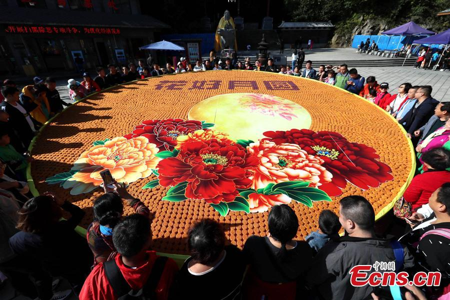 Staff members at Laojun Mountain, a scenic spot in Luoyang City, Central China\'s Henan Province, use 9,999 colorful mooncakes to spell out a beautiful pattern with Chinese characters of Hua Hao Yue Yuan (Blooming flowers and full moon) to celebrate the Mid-Autumn Festival, Sept. 23, 2018. (Photo: China News Service/Wang Zhongju)