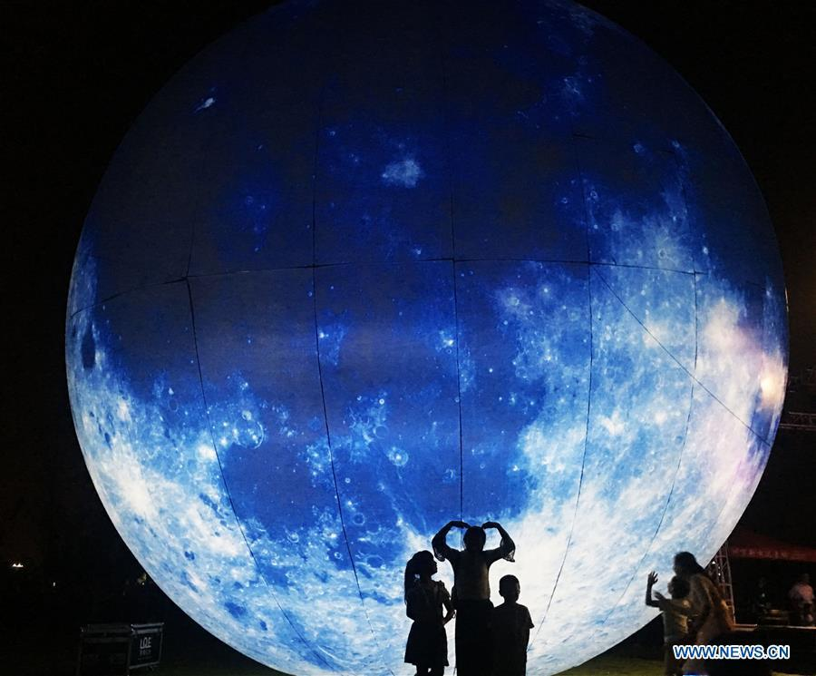 Pedestrians pose for photos with a moon installation set up to mark the upcoming Mid-Autumn Festival in Bozhou, east China\'s Anhui Province, Sept. 23, 2018. (Xinhua/Ni Shubin)