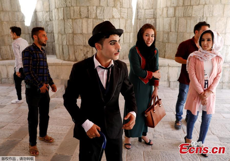 Afghanistan\'s Charlie Chaplin, Karim Asir, 25, talks with his fans before his performance in Kabul, Afghanistan, Aug. 29, 2018. Karim Asir says he has witnessed suicide attacks, explosions and threats from hardline Islamic militant groups, but is determined to waddle and bumble to fulfill the primary goal of his life. (Photo/Agencies)