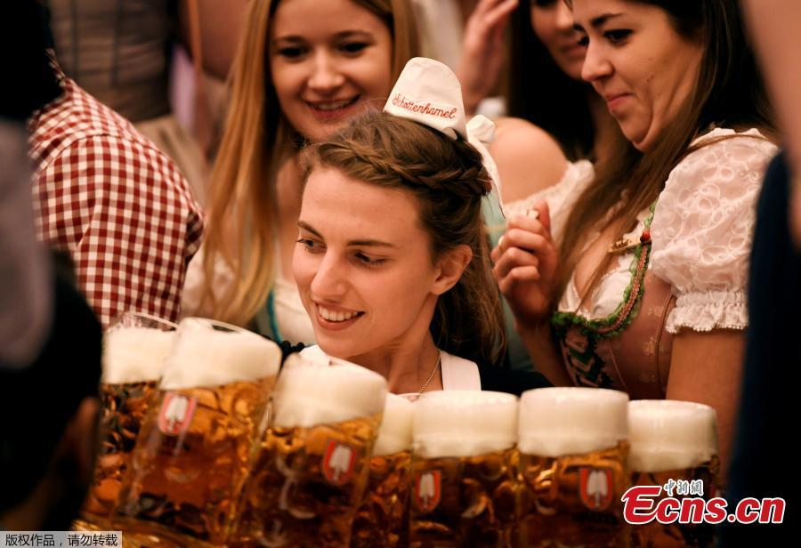 Visitors cheer with beers during the 185th Oktoberfest in Munich, Germany. Thousands of visitors, many of them dressed in traditional lederhosen or dirndl corseted dresses, descended on Munich on Saturday for the start of the annual Oktoberfest, the world's largest beer festival. Oktoberfest is the world\'s largest beer celebration and typically draws over six million visitors over its three-week run. Oktoberfest includes massive beer tents, each run by a different Bavarian brewer, as well as amusement rides and activities.  (Photo/Agencies)