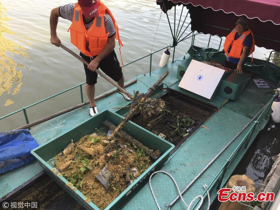 A boat equipped with a new device collects garbage in a river in Pingyang County, East China's Zhejiang Province, Sept. 25, 2018. The rope-like electronic devices can be remotely controlled to rise above or fall under the water to collect floating garbage. (Photo/VCG)