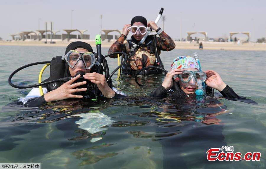 Saudi female divers Maryam Ahmed Al-Moalem (L), Zynab Al Magaslah (C) and Fatimah Al Saeed (R) prepare to deflate their BCDs (buoyancy control devices) to dive in the sea at Half Moon Beach open-water dive site in Dhahran, Saudi Arabia, Sept. 15, 2018. (Photo/Agencies)