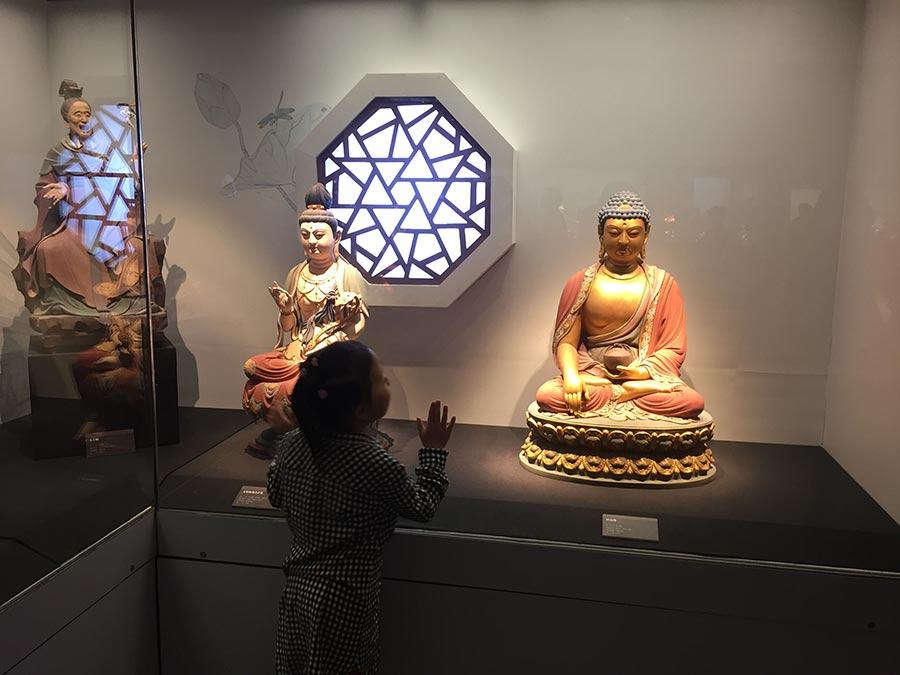 A child looks at colored sculpture shown at the exhibition. 