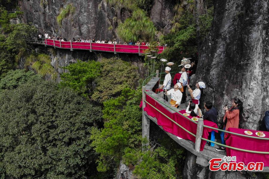 Chefs show stunt skills with kitchenware at a restaurant built on a cliff at Longquan Mountain in Zhejiang Province, Sept. 27, 2018. The restaurant 1,600 meters above sea level allows customers to dine on suspended plank roads while enjoying great views of the mountain. Longquan is the highest peak in the Yangtze River Delta. (Photo: China News Service/Yang Yong)