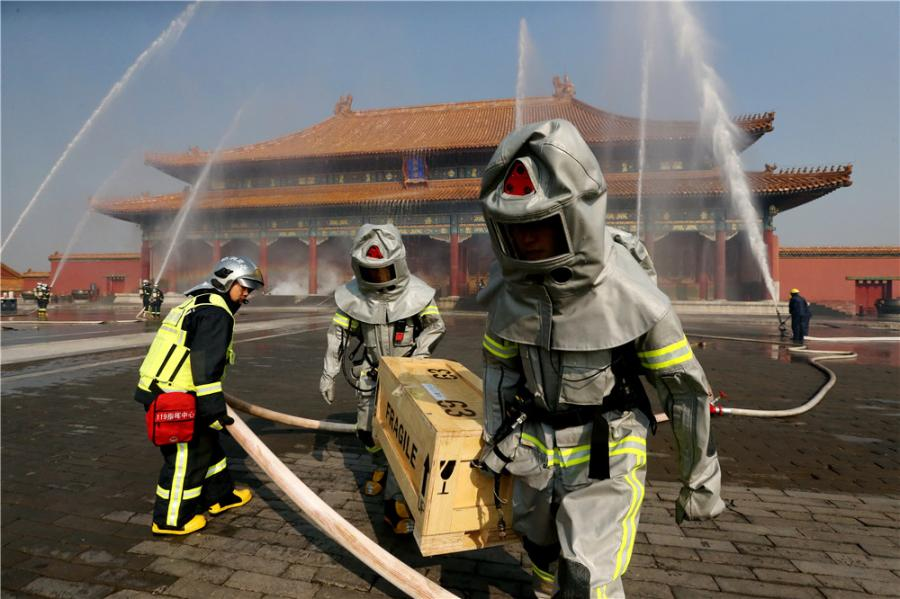 Drills are staged frequently at the Palace Museum in Beijing, where a team is stationed by the east gate to keep watch for fire in turn 24 hours a day. (Photo/CHINA DAILY)  Tests are held every week. Firefighters have to run more than 50 meters within 13 seconds carrying three rolls of 20-meter-long standpipe hoses and connecting them.  Strict practice is essential to remaining vigilant.  Firefighters stationed in residential areas may be called out to fires every day. However, since the Tiananmen Fire Squadron was set up in 1970, there have been no major fires within its 3.74-sq-km jurisdiction, which covers not only the Palace Museum but all of Tiananmen Square.  In 1987, the Palace of Great Brilliance (Jingyanggong) at the museum was hit by lightning and caught fire. The blaze was quickly put out before any damage was caused to cultural relics, although a small part of the roof was charred. After this, lightning conductors were installed on the roofs of all the buildings at the complex.  Du said: \
