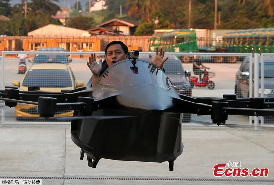 """Kyxz Mendiola gestures after testing his flying car invention in the province of Batangas, Philippines, September 23, 2018. Former dancer and camera operator Kyxz Mendiola flew and hovered for a few minutes in a single-passenger contraption powered by the """"multicopter"""" technology commonly used in small unmanned drones. (Photo/Agencies)"""