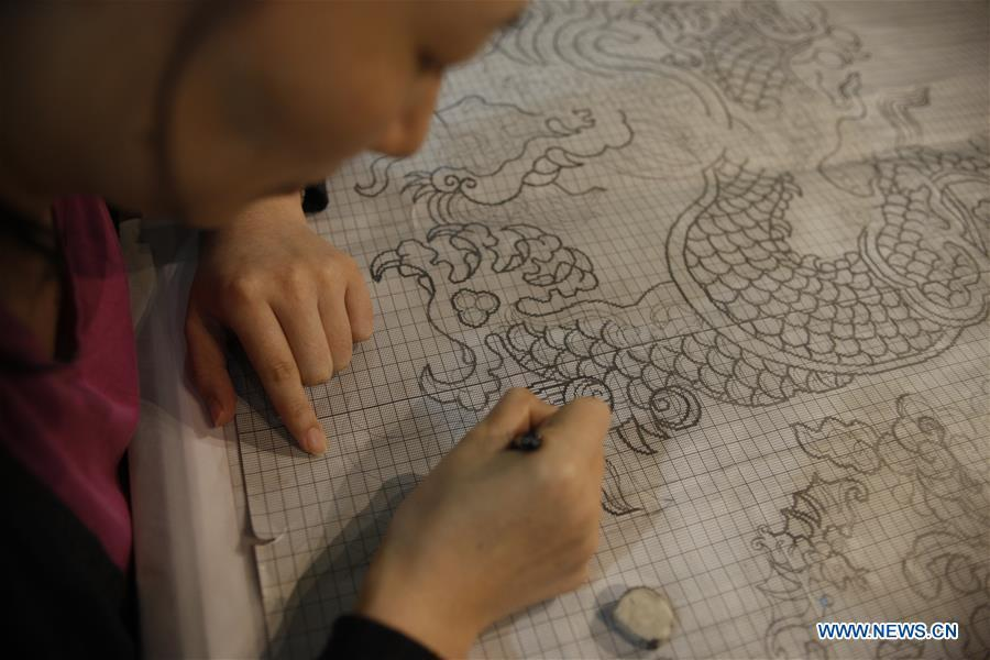 A weaver draws a pattern before weaving Yun brocade at the Nanjing Yunjin Museum in Nanjing, capital of east China\'s Jiangsu Province, Sept.26, 2018. Yunjin, also called Yun brocade, is traditional Chinese silk brocade made in Nanjing of Jiangsu. Dated from the Eastern Jin Dynasty, it has formed its own characteristics through its development of 1,600 years. Yun brocade is famous for its exquisite craft, elegant patterns and smooth texture, and the making of the artwork requires close cooperation of two weavers, who can produce only five centimeters a day. In 2009, Yun brocade was inscribed on the Representative List of the Intangible Cultural Heritage of Humanity. (Xinhua/Zhu Weixi)