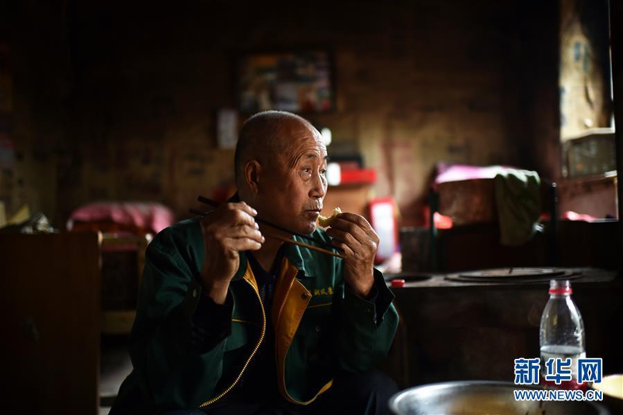 Zhao Naitang, 73, has lunch at the Huangyadong Martyrs Cemetery in Licheng County, North China's Shanxi Province, Sept. 18, 2018. Huangyadong used to be an arsenal of the Eighth Route Army and a battlefield during the Chinese People\'s War of Resistance against Japanese Aggression. Zhao has been the custodian at the cemetery, where 44 martyrs were buried, since 1991. (Photo/Xinhua)