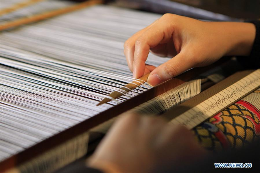 A weaver shows skills of weaving Yun brocade at the Nanjing Yunjin Museum in Nanjing, capital of east China\'s Jiangsu Province, Sept.26, 2018. Yunjin, also called Yun brocade, is traditional Chinese silk brocade made in Nanjing of Jiangsu. Dated from the Eastern Jin Dynasty, it has formed its own characteristics through its development of 1,600 years. Yun brocade is famous for its exquisite craft, elegant patterns and smooth texture, and the making of the artwork requires close cooperation of two weavers, who can produce only five centimeters a day. In 2009, Yun brocade was inscribed on the Representative List of the Intangible Cultural Heritage of Humanity. (Xinhua/Sui Xiankai)
